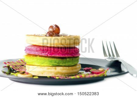 stack of pancakeswith grape in black dish isolate on white background