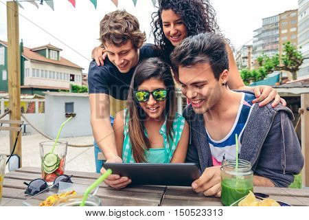 Young happy people looking electronic tablet sitting around of table with healthy drinks in a summer day outdoors. Young people lifestyle concept.