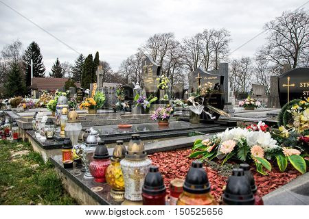 TVRDOMESTICE SLOVAKIA - 12.3.2016: Graves tombstones and crucifixes on traditional cemetery. Votive candles lantern and flowers on tomb stones in graveyard. Gravestones in small village