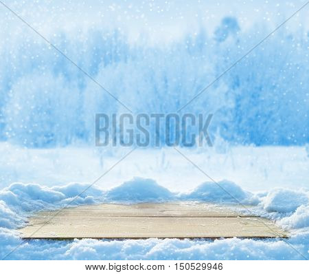 Winter background with snow-covered wooden table and beautiful forest
