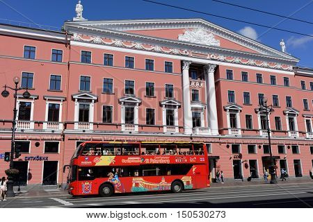 ST. PETERSBURG, RUSSIA - AUGUST 8, 2016: Double-decker sightseeing tour bus against the Literary house on Nevsky avenue. The house was built in 1947-1950