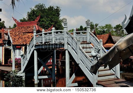 Samut Prakan Thailand - January 15 2013: A wooden bridge spans a lagoon at the Floating Market and Water Village at Ancient Siam Heritage Park