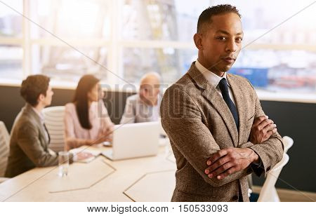 Mixed race businessman standing with his arms crossed in front of three other colleagues that are sitting at the table behind him.