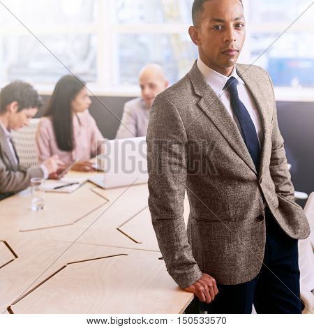 Well dressed mixed race businessman leaning against board room table while standing in front of his other three colleagues that are seated behind him.
