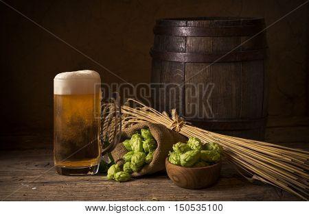glass of beer with hop cones weather, wooden