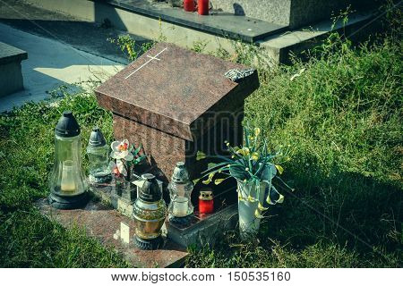 Urn grave with cross on traditional cemetery. Votive candles lantern and flowers on tomb stones in graveyard. All Saints' Day. All Souls' Day. Gravestones in village Tvrdomestice Slovakia