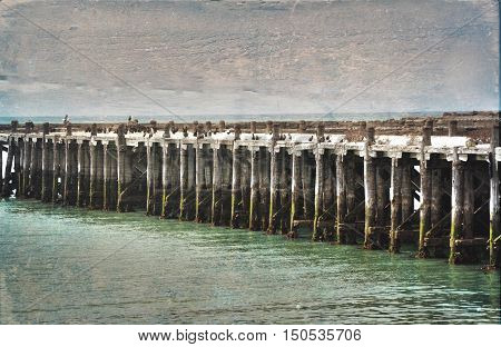 Historic old wooden Sumpter Wharf at Oamaru Harbour, New Zealand. Vintage, grunge textured image. Roosting site for colony of shags (waterbirds).
