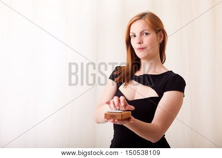 Woman with red hair and a Kalimba