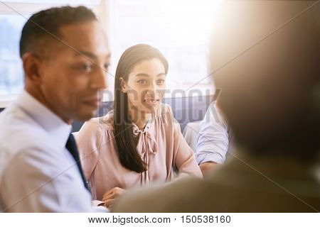 Attractive businesswoman and businessman paying attention to senior business woman during a meeting, shot over the shoulder of the business woman.