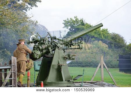 Dover United Kingdom - October 1 2016: Man firing world war two anti aircraft gun in re-enactment