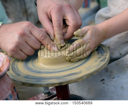 Hands working on pottery wheelin a art scool