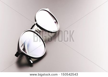 Black satine plastic circle eye glasses for womenor hipster, lying on grey background with accurate shadow.