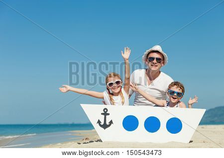 Father and children playing on the beach at the day time. People having fun on nature. Concept of friendly family.