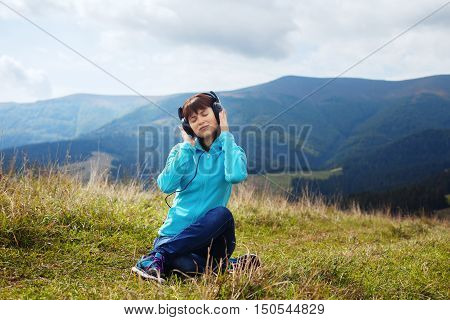 girl listening to music in the mountains and relaxes. The concept of travel and lifestyle.