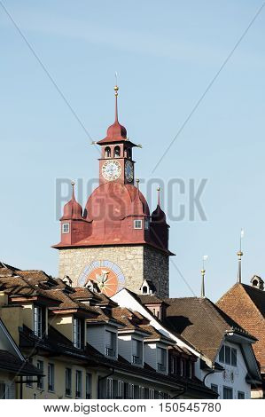 LUCERNE SWITZERLAND - MAY 04 2016: Clock tower that is a part of Town Hall towering over other city buildings. The Clock Tower with its huge clock is height over 40 meters.