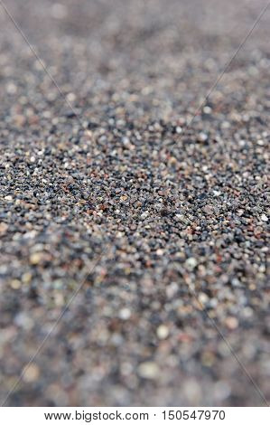 Dry black volcanic sand from Santorini background. Selective focus.