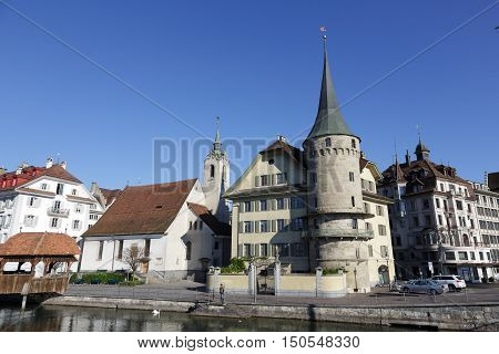 LUCERNE SWITZERLAND - MAY 05 2016: Haus zur Gilgen one of the oldest stone houses in the city and St. Peter Chapel both buildings are located on the right bank of river Reuss