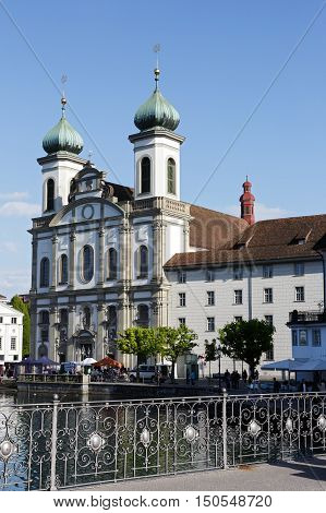 LUCERNE SWITZERLAND - MAY 04 2016: View of towards Jesuit Church located by the Reuss river in old town. This church is one of the most visited tourist attractions in the city