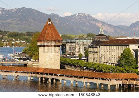 LUCERNE SWITZERLAND - MAY 04 2016: Landscape of the city including its most recognizable landmarks. Octagonal tower that was built in the river Reuss and the roofed Chapel Bridge can be seen.
