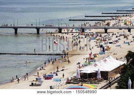 KOLOBRZEG POLAND - JUNE 22 2016: Many unidentified vacationers enjoys their spare time at the sandy beach in the immediate vicinity of the pier by the Polish coast of the Baltic Sea.