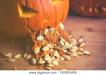 Close Up On Pumpkin Puking With Pumpkin Seeds On Wood Table