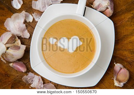 Garlic Cream Soup In Orange Bowl On Wooden Background. Rustic Country Style. Top View