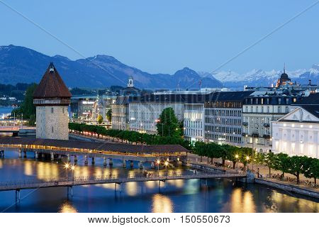 LUCERNE SWITZERLAND - MAY 06 2016: Night view towards the tower that was built in the river Reuss and is next to the roofed Chapel Bridge. Buildings on the left bank of the river can be seen.