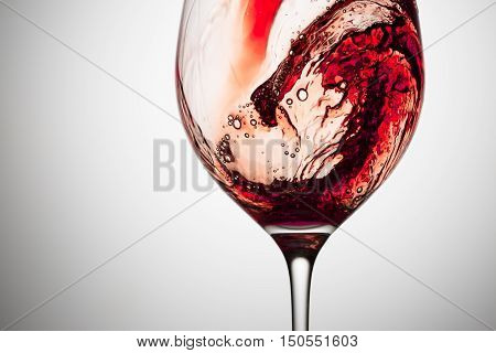 Stream of wine being pouring into a glass. Closeup splash of wine.