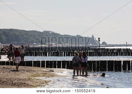 KOLOBRZEG POLAND - JUNE 29 2016: Several unidentified vacationers spend their spare time at the shoreline of the Baltic Sea and they enjoy with the evening