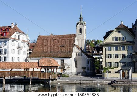 LUCERNE SWITZERLAND - MAY 05 2016: St. Peter Chapel is located by the Reuss river in the Chapel square in the old town next to famous chapel bridge and it is one of the many tourist attractions