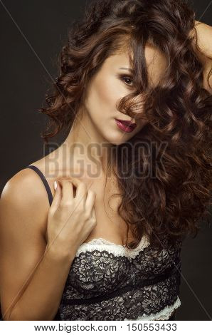 portrait of the curly-headed mysterious girl with a ringlet of hair in the person in underwear the studio photo