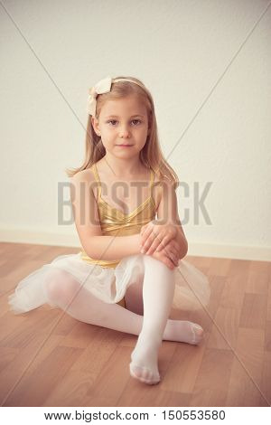 Pretty Diligent Ballet Girl Sitting In White Tutu At Dance Studio