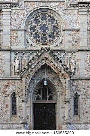 front einer katholischen kirche mkit eingangstür und rundfenster