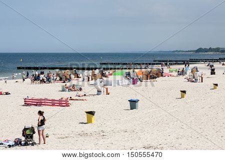 KOLOBRZEG POLAND - JUNE 19 2016: Unidentified tourists enjoys the time that they spend by the Baltic sea. They are sunbathing strolling and they have relax