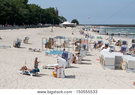 KOLOBRZEG POLAND - JUNE 19 2016: Unidentified vacationers enjoy the sunny weather they are relaxing and sunbathing on the shore of the Baltic Sea many of them use roofed beach chairs