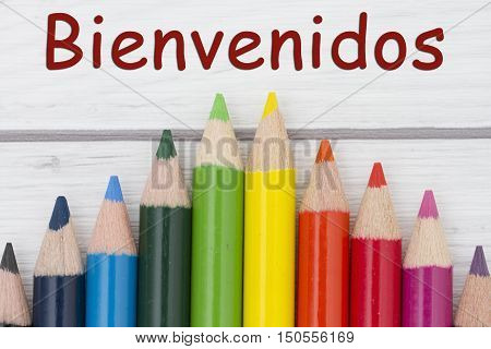 Pencil Crayons with text Bienvenidos Spanish for Welcome with weathered wood background
