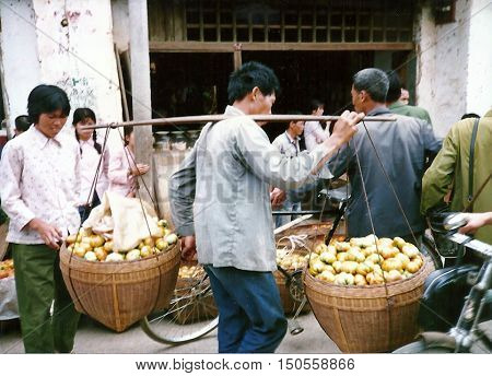 GUILIN / CHINA - CIRCA 1987: A man carries two heavy baskets full of squashes past sidewalk vendors selling fresh vegetables in Guilin.