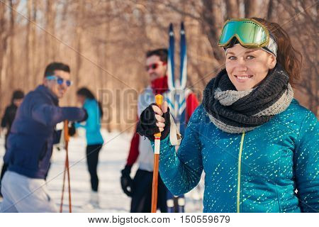 Group of millenial young adult friends relaxing with ski equipment in a snow filled park