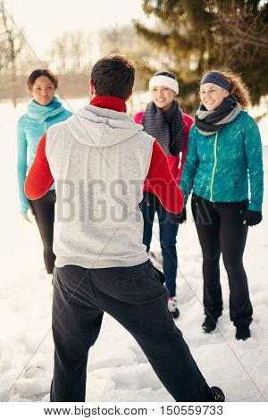 Group of millenial young adult friends stretch and strengthen in a snow filled park