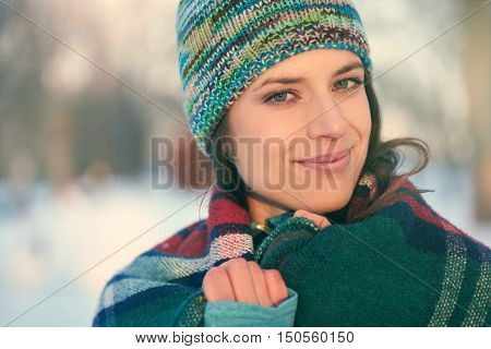 Serene lady relaxing wrapped in  plad blanket in winter