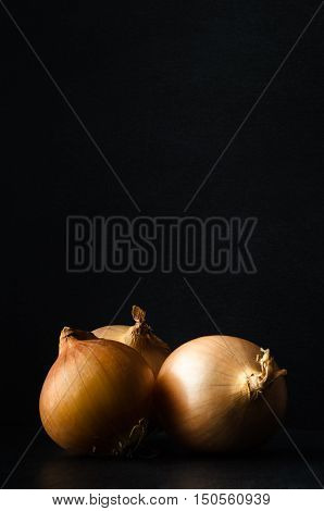 Three Whole Onions On Slate With Black Chalkboard Background