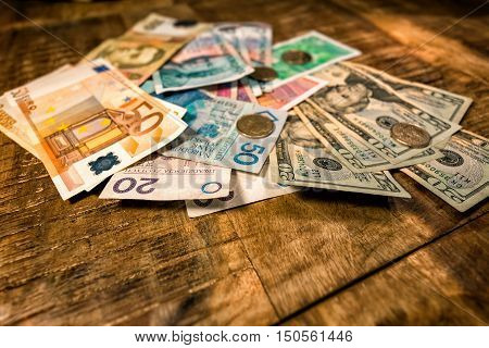 paper money of different denominations and different countries spread out on the table
