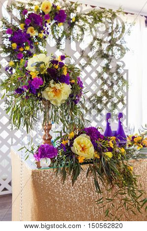 Floral arrangement to decorate wedding table in purple color. The vintage.