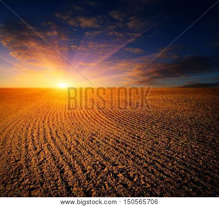 Landscape with sunset over ploughed farming field