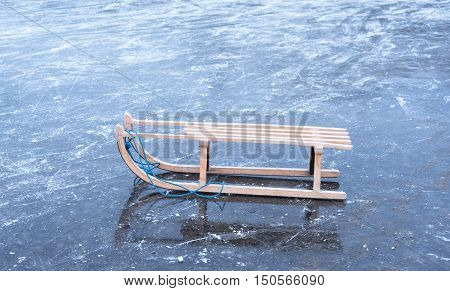 Wooden sled on dirty ice a winters day