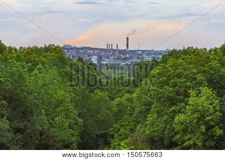 Clean green forest in the background polluting the air industrial factory. Plant in green ravine smog behind. Industrial plant in smog behind green trees. Cement factory. Environmental pollution.