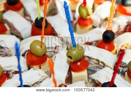Canapes - small sandwiches on skewers on a plate close. Culinary food buffets. Sandwiches of toast, cut and different food base (fish, meat, cheese) impaled on Atle.