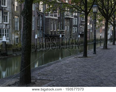 The canal Pottenkade in Dordrecht in Zuid-Holland The Netherlands with old monumental houses and nostalgic street lamp in the evening.