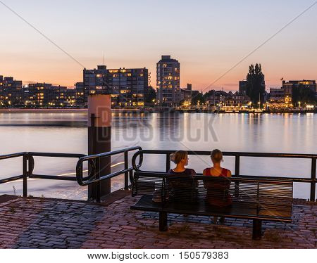Dordrecht The Netherlands - September 13 2016: Two people on a bench in the evening light at the river Merwede in Dordrecht The Netherlands.