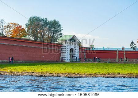 ST PETERSBURG RUSSIA - OCTOBER 3 2016. Ioannovsky or St John gates and Ioannovsky bridge to the Peter and Paul fortress in St Petersburg Russia and tourists walking along